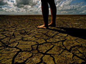bare feet on dry, cracked soil